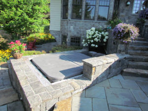 Tucked away hot tub finished with stone surround by Carpenter & Costin