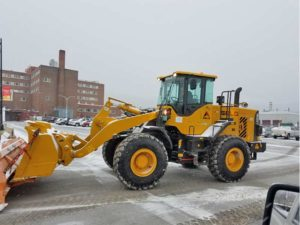 Front end loader plowing snow