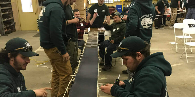 Men in sweatshirts building a model bridge
