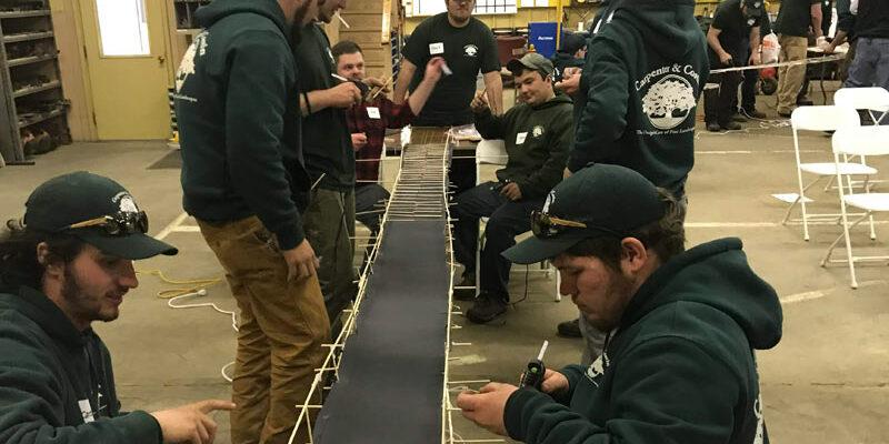 Men in sweatshirts building a model bridge