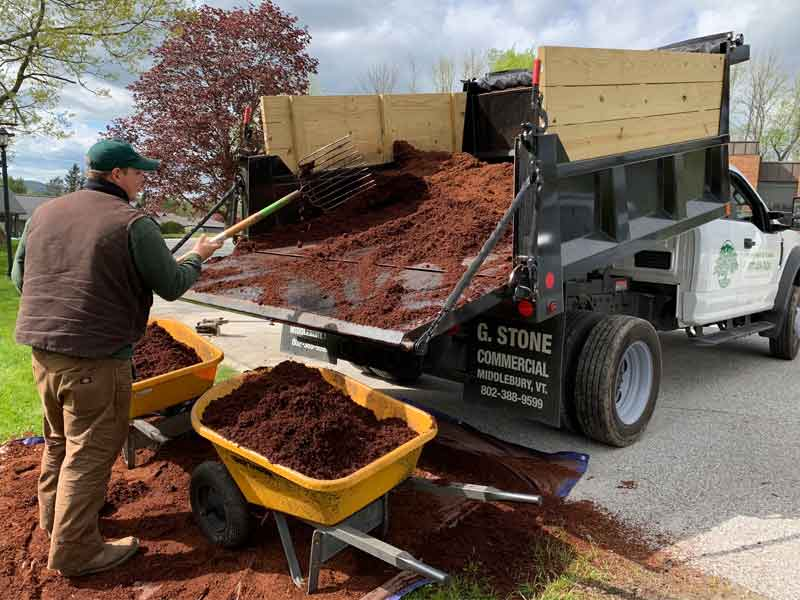Man unloading mulch from dump truck